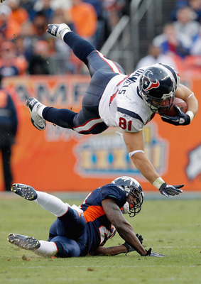 DENVER - DECEMBER 26:  Tight end Owen Daniels #81 of the Houston Texans gets up-ended by cornerback Andre' Goodman #21 of the Denver Broncos during the first quarter at INVESCO Field at Mile High on December 26, 2010 in Denver, Colorado. (Photo by Justin