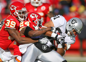 KANSAS CITY, MO - JANUARY 02:  Wide receiver Chaz Schilens #81 of the Oakland Raiders is tackled by Brandon Carr #39 and Brandon Flowers #24 of the Kansas City Chiefs in a game at Arrowhead Stadium on January 2, 2011 in Kansas City, Missouri.  (Photo by T