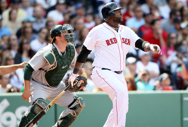 BOSTON, MA - JUNE 04:  David Ortiz #34 of the Boston Red Sox hits a double in the eighth inning as Landon Powell #11 of the Oakland Athletics catches on June 4, 2011 at Fenway Park in Boston, Massachusetts.  (Photo by Elsa/Getty Images)