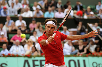 PARIS, FRANCE - JUNE 03:  Roger Federer of Switzerland hits a backhand during the men's singles semi final match between Roger Federer of Switzerland and Novak Djokovic of Serbia on day thirteen of the French Open at Roland Garros on June 3, 2011 in Paris