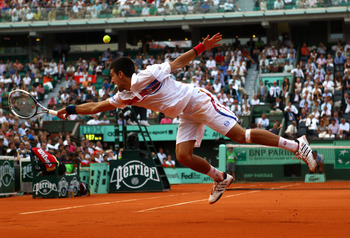 PARIS, FRANCE - JUNE 03:  Novak Djokovic of Serbia stretches to hit a backhand during the men's singles semi final match between Roger Federer of Switzerland and Novak Djokovic of Serbia on day thirteen of the French Open at Roland Garros on June 3, 2011