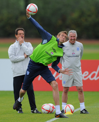 ST ALBANS, ENGLAND - MAY 31: Peter Crouch throws the ball as England manager Fabio Capello looks on during the England training session at London Colney on May 31, 2011 in St Albans, England.  (Photo by Michael Regan/Getty Images)