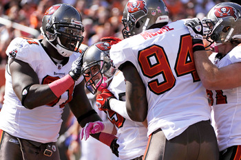 CINCINNATI, OH - OCTOBER 10:  Stylez G. White #91 and Kyle Moore #94 of the Tampa Bay Buccaneers celebrate with teammate Cody Grimm #35 of the Buccaneers after Grimm's 11-yard interception return for a touchdown in the first half against the Cincinnati Be