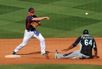 GOODYEAR, AZ - MARCH 11:  Cord Phelps #73 of the Cleveland Indians turns a double play over the top of a sliding Carlos Peguero #64 of the Seattle Mariners at Goodyear Ballpark on March 11, 2011 in Goodyear, Arizona.  (Photo by Norm Hall/Getty Images)