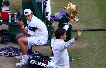 WIMBLEDON, ENGLAND - JULY 05:  Andy Roddick of USA looks despondent as Roger Federer of Switzerland celebrates with the trophy during the men's singles final match on Day Thirteen of the Wimbledon Lawn Tennis Championships at the All England Lawn Tennis a