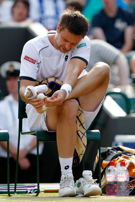 LONDON, ENGLAND - JUNE 30:  Robin Soderling of Sweden checks his foot between games during his Quarter Final match against Rafael Nadal of Spain on Day Nine of the Wimbledon Lawn Tennis Championships at the All England Lawn Tennis and Croquet Club on June