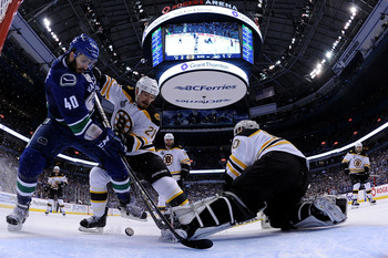 VANCOUVER, BC - JUNE 04:  Maxim Lapierre #40 of the Vancouver Canucks and Andrew Ference #21 of the Boston Bruins fight for the puck in front of Tim Thomas #30 of the Boston Bruins during Game Two of the 2011 NHL Stanley Cup Final at Rogers Arena on June