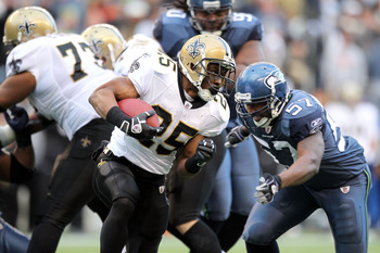 SEATTLE, WA - JANUARY 08:  Reggie Bush #25 of the New Orleans Saints runs the ball against David Hawthorne #57 of the Seattle Seahawks in the third quarter during the 2011 NFC wild-card playoff game at Qwest Field on January 8, 2011 in Seattle, Washington