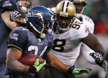 SEATTLE, WA - JANUARY 08:  Marshawn Lynch #24 of the Seattle Seahawks runs down field against Sedrick Ellis #98 of the New Orleans Saints during the 2011 NFC wild-card playoff game at Qwest Field on January 8, 2011 in Seattle, Washington.  (Photo by Otto