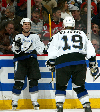 EAST RUTHERFORD, NJ - APRIL 14:  Martin St. Louis #26 of the Tampa Bay Lightning celebrates his goal with teammate Brad Richards #19 as Scott Gomez #23 of the New Jersey Devils skates by during the second period of Game 2 of the 2007 Eastern Conference Qu