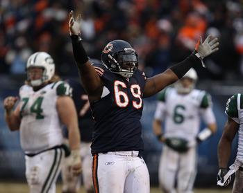 CHICAGO, IL - DECEMBER 26: Henry Melton #69 of the Chicago Bears celebrates after teammate Chris Harris intercepted a pass in the final minutes as Nick Mangold #74 and Mark Sanchez #6 of the New York Jets walk off of the field at Soldier Field on December