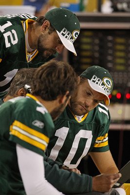 GREEN BAY, WI - AUGUST 26: (L-R) Graham Harrell #7, Aaron Rodgers #12 and Matt Flynn #10 of the Green Bay Packers look over plays on the bench during a preseason game against the Indianapolis Colts at Lambeau Field on August 26, 2010 in Green Bay, Wiscons