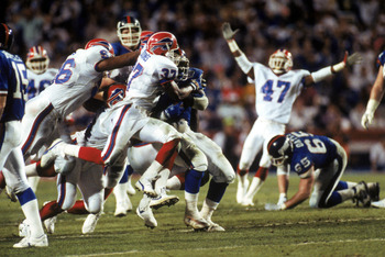 TAMPA, FL - JANUARY 27:  Cornerback Nate Odomes #37 of the Buffalo Bills tackles running back Ottis Anderson #24 of the New York Giants during Super Bowl XXV at Tampa Stadium on January 27, 1991 in Tampa, Florida. The Giants defeated the Bills 20-19.  (Ph