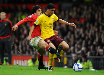 MANCHESTER, ENGLAND - MARCH 12: Rafael Da Silva of Manchester United and Denilson of Arsenal battle for the ball during the FA Cup sponsored by E.On Sixth Round match between Manchester United and Arsenal at Old Trafford on March 12, 2011 in Manchester, E