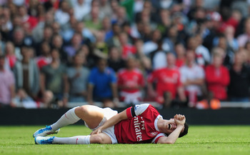 LONDON, ENGLAND - APRIL 17:  Samir Nasri of Arsenal lies injured on the pitch after a harsh tackle by John Flanagan of Liverpool during the Barclays Premier League match between Arsenal and Liverpool at the Emirates Stadium on April 17, 2011 in London, En