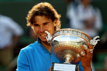 PARIS, FRANCE - JUNE 05:  Champion Rafael Nadal of Spain bites the trophy following his record equalling sixth victory during the men's singles final match between Rafael Nadal of Spain and Roger Federer of Switzerland on day fifteen of the French Open at