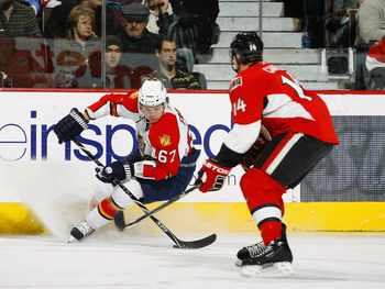 OTTAWA, ON - JANUARY 9:  Michael Frolik #67 of the Florida Panthers stops hard along the far boards with the puck while being watched by Chris Campoli #14 of the Ottawa Senators in a game at Scotiabank Place on January 9, 2010 in Ottawa, Canada.  (Photo b