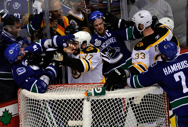 VANCOUVER, BC - JUNE 01:  Alex Burrows #14 of the Vancouver Canucks fights with Patrice Bergeron #37 of the Boston Bruins as Henrik Sedin #33 of the Vancouver Canucks and Zdeno Chara #33 of the Boston Bruins fight during game one of the 2011 NHL Stanley C
