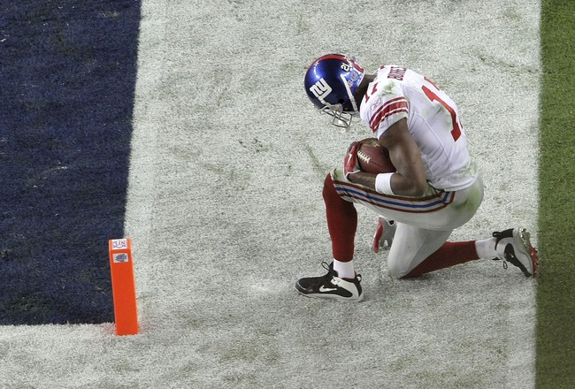 GLENDALE, AZ - FEBRUARY 03:  Plaxico Burress #17 of the New York Giants kneels just outside the endzone after he scored on a 13-yard touchdown reception in the fourth quarter against the New England Patriots during Super Bowl XLII on February 3, 2008 at t