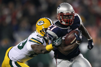 FOXBORO, MA - DECEMBER 19:  Cornerback Kyle Arrington #27 of the New England Patriots evades wide receiver James Jones #89 of the Green Bay Packers to run the ball 36 yards and score a touchdown during the third quarter of the game at Gillette Stadium on 