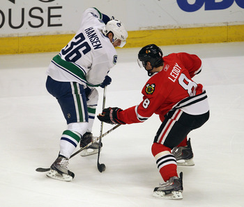CHICAGO, IL - APRIL 19: Jannik Hansen #36 of the Vancouver Canucks controls the puck under pressure from Nick Leddy #8 of the Chicago Blackhawks in Game Four of the Western Conference Quarterfinals during the 2011 NHL Stanley Cup Playoffs at the United Ce
