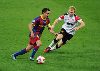 LONDON, ENGLAND - MAY 28:  Xavi of FC Barcelona is watched by Paul Scholes of Manchester United during the UEFA Champions League final between FC Barcelona and Manchester United FC at Wembley Stadium on May 28, 2011 in London, England.  (Photo by Michael