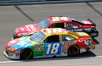 KANSAS CITY, KS - JUNE 05:  Kyle Busch, driver of the #18 M&M's Toyota, races Jeff Gordon, driver of the #24 Drive to End Hunger Chevrolet, during the NASCAR Sprint Cup Series STP 400 at Kansas Speedway on June 5, 2011 in Kansas City, Kansas.  (Photo by G