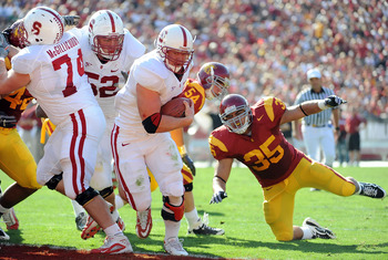 LOS ANGELES, CA - NOVEMBER 14:  Toby Gerhart #7 of the Stanford Cardinal runs in for a touchdown past a fallen Uona Kaveinga #35 of the USC Trojans for a 14-0 lead during the first half at the Los Angeles Memorial Coliseum on November 14, 2009 in Los Ange