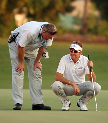 DUBAI, UNITED ARAB EMIRATES - NOVEMBER 28:  Ian Poulter of England with refree Andy McFee as a penlaty shot is called during the second play-off hole during the play-off during the final round of the Dubai World Championship on the Earth Course, Jumeirah