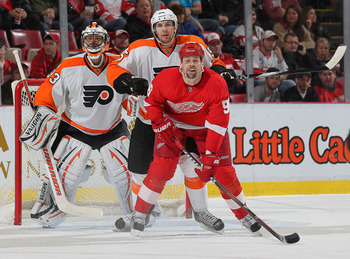 DETROIT, MI - JANUARY 2:  Brayden Coburn #5 of the Philadelphia Flyers gives Tomas Holmstrom #96 of the Detroit Red Wings a shot in the back in a game on January 2, 2011 at the Joe Louis Arena in Detroit, Michigan. The Flyers defeated the Wings 3-2. (Phot