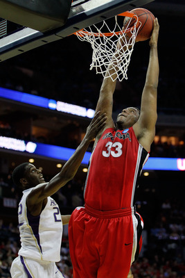 CHARLOTTE, NC - MARCH 18:  Trey Thompkins #33 of the Georgia Bulldogs goes up for a dunk over Justin Holiday #22 of the Washington Huskies in the first half during the second round of the 2011 NCAA men's basketball tournament at Time Warner Cable Arena on