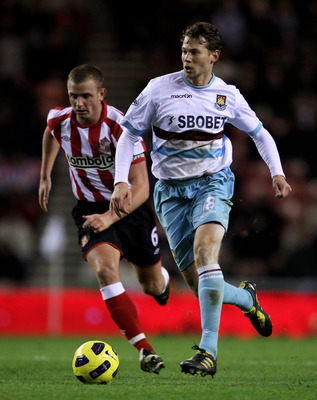 SUNDERLAND, ENGLAND - DECEMBER 05:  Lee Cattermole of Sunderland competes for the ball with Jonathan Spector of West Ham United during the Barclays Premier League match between Sunderland and West Ham United at the Stadium of Light on December 5, 2010 in