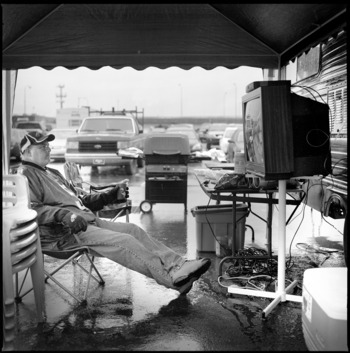 PHILADELPHIA - NOVEMBER 18:  Tailgater Joe Hammond sits in the rain watching the Miami Dolphins play against the Philadelphia Eagles on his make shift tv in the stadium carpark after giving away his ticket to a friends son, during the NFL game between the