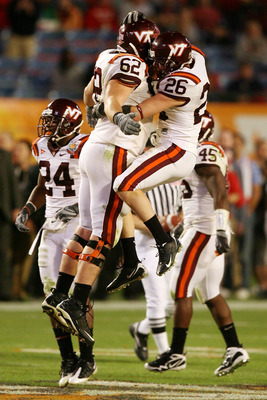 MIAMI - JANUARY 01:  Blake DeChristopher #62 and  Cody Grimm #26 of the Virginia Tech Hokies celebrates against the Cincinnati Bearcats during the FedEx Orange Bowl at Dolphin Stadium on January 1, 2009 in Miami, Florida.  (Photo by Doug Benc/Getty Images