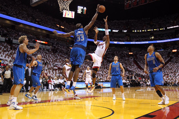 MIAMI, FL - MAY 31:  Chris Bosh #1 of the Miami Heat shoots over Brendan Haywood #33 of the Dallas Mavericks in the second half in Game One of the 2011 NBA Finals at American Airlines Arena on May 31, 2011 in Miami, Florida. NOTE TO USER: User expressly a