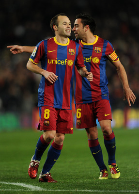 BARCELONA, SPAIN - JANUARY 22:  Andres Iniesta (L) of Barcelona runs past his teammate Xavi Hernandez after scoring his sides third goal during the la liga match between Barcelona and Racing Santander at the Camp Nou stadium on January 22, 2011 in Barcelo