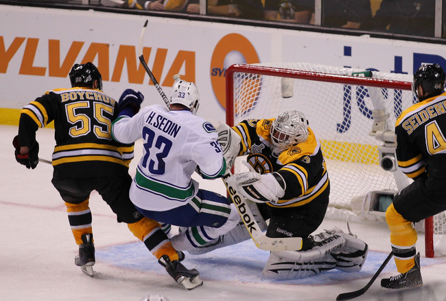 BOSTON, MA - JUNE 06:  Tim Thomas #30 of the Boston Bruins checks Henrik Sedin #33 of the Vancouver Canucks as he tends goal during Game Three of the 2011 NHL Stanley Cup Final at TD Garden on June 6, 2011 in Boston, Massachusetts.  (Photo by Jim Rogash/G