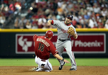 PHOENIX, AZ - JUNE 05:  Infielder Danny Espinosa #18 of the Washington Nationals throws over the sliding Willie Bloomquist #18 of the Arizona Diamondbacks to complete a double play during the thrid inning of the Major League Baseball game at Chase Field o