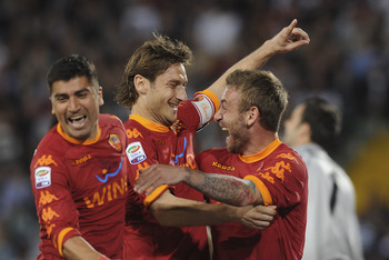 UDINE, ITALY - APRIL 09:  Francesco Totti (C) of Roma celebrates with teams mates Daniele De Rossi and David Pizarro  after scoring  his opening penalty goal  during the Serie A match between Udinese Calcio and AS Roma at Stadio Friuli on April 9, 2011 in