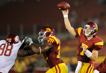 LOS ANGELES, CA - SEPTEMBER 26:   Quarterback Matt Barkley #7 of the USC Trojans throws a pass as Tyron Smith #70 blocks Jesse Feagin #98 of  the Washington State Cougars during the second quarter of the college football game at the Los Angeles Memorial C