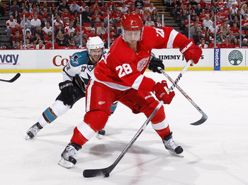 DETROIT - MAY 6: Brian Rafalski #28 of the Detroit Red Wings controls the puck in front of Torrey Mitchell #17 of the San Jose Sharks during the third period in Game Four of the Western Conference Semifinals during the 2011 NHL Stanley Cup Playoffs on May