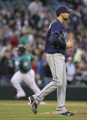 SEATTLE - JUNE 03:  Miguel Olivo #30 of the Seattle Mariners rounds third base after hitting a home run off of starting pitcher Andy Sonnanstine #21 (foreground) of the Tampa Bay Rays at Safeco Field on June 3, 2011 in Seattle, Washington. (Photo by Otto