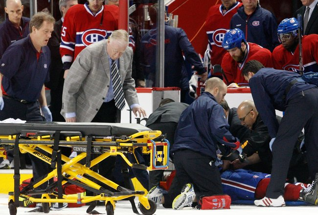 MONTREAL, CANADA - MARCH 8:  Members of the Montreal Canadiens medical staff tend to Max Pacioretty #67 of the Montreal Canadiens after being hit by Zdeno Chara #33 of the Boston Bruins (not pictured) during the NHL game at the Bell Centre on March 8, 201