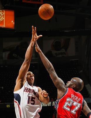 ATLANTA, GA - DECEMBER 07:  Al Horford #15 of the Atlanta Hawks shoots over Johan Petro #27 of the New Jersey Nets at Philips Arena on December 7, 2010 in Atlanta, Georgia.  NOTE TO USER: User expressly acknowledges and agrees that, by downloading and/or