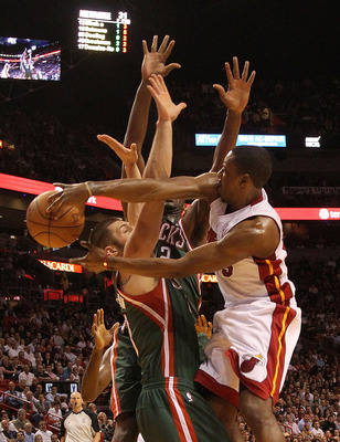 MIAMI, FL - JANUARY 04: Mario Chalmers #15 of the Miami Heat passes the ball over Jon Brockman #40 of the Milwaukee Bucks during a game at American Airlines Arena on January 4, 2011 in Miami, Florida. NOTE TO USER: User expressly acknowledges and agrees t