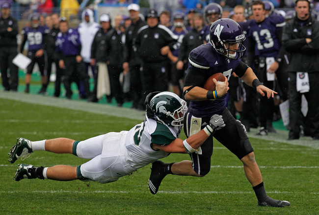 EVANSTON, IL - OCTOBER 23: Dan Persa #7 of the Northwestern Wildcats escapes a tackle attempt by Eric Gordon #43 of the Michigan State Spartans at Ryan Field on October 23, 2010 in Evanston, Illinois. Michigan State defeated Northwestern 35-27.  (Photo by