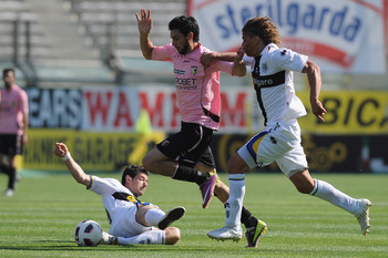 PARMA, ITALY - MAY 01:   Javier Matias Pastore of US Citta di Palermo is challenged by Blerin Dzemaili (L) and Rolf Gunther Feltscher Martinez (R) of Parma FCduring the Serie A match between Parma FC and US Citta di Palermo at Stadio Ennio Tardini on May