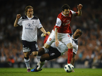 LONDON, ENGLAND - APRIL 20:  Cesc Fabregas of Arsenal is tackled by Tom Huddlestone of Spurs during the Barclays Premier League match between Tottenham Hotspur and Arsenal at White Hart Lane on April 20, 2011 in London, England.  (Photo by Laurence Griffi