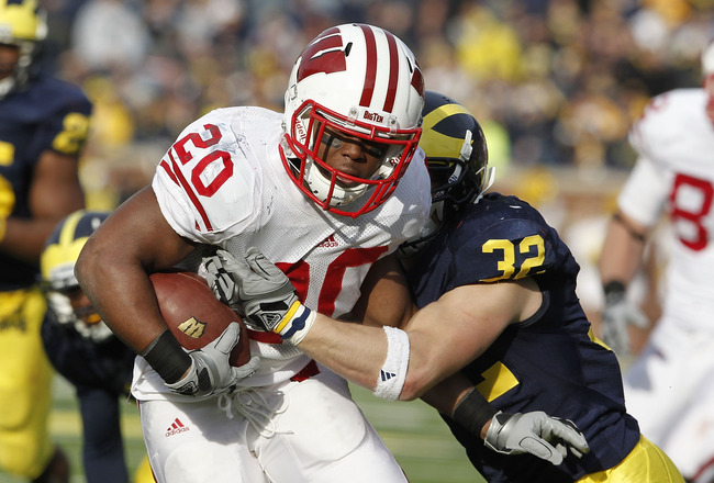 ANN ARBOR, MI - NOVEMBER 20:  James White #20 of the Wisconsin Badgers treies to get around the tackle of Jordan Kovacs #32 of the Michigan Wolverines at Michigan Stadium on November 20, 2010 in Ann Arbor, Michigan. Wisconson won the game 48-28.  (Photo b