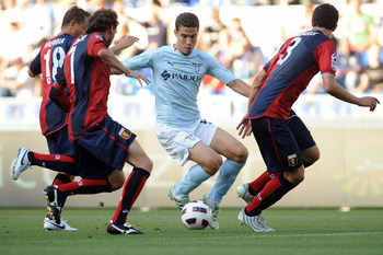 ROME, ITALY - MAY 14:  Anderson Hernanes of SS Lazio in action against Rafinha Ferreira (L), Marco Rossi (C) and Dario Dainelli (R) of Genoa CFC during the Serie A match between SS Lazio and Genoa CFC at Stadio Olimpico on May 14, 2011 in Rome, Italy.  (P